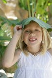 Leafy Hat. A little girl on vacation wearing a leaf like a hat on her head Royalty Free Stock Image