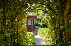 Leafy hedge gate and pathway to modern brick house royalty free stock photo