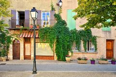 Leafy house fronts with shuttered windows, Provence, France. Traditional house fronts with wooden shuttered windows and leafy facade, Provence, France stock image
