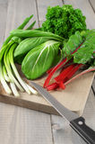 Leafy vegetables on cutting board Stock Photos