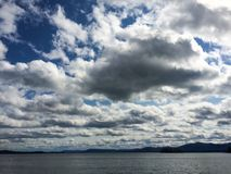Leagues of Angels. A bright sunny day on Lake Champlain in Vermont with thick puffy bright clouds going deep into the horizon Stock Photo