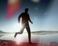 Leakage of light in the lens. . Running man. Sportsman run, jogging guy during the sunrise above sandy beach. Stock Photography