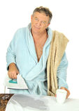 Leaking Iron Man. Middle aged man in bath robe with a cup of tea deals with a leaking steam iron Stock Photography