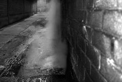 Leaking steam pipe. Black and white picture of a leaking steam pipe in an alleyway of a factory Stock Photography