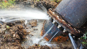 Leaking water pipe. Broken pipeline with large amount of leaking water Royalty Free Stock Image