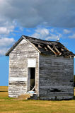 Leaky Roof. Storm clouds hover over a dilapidated building with holes in the roof and a single seagull perched on the top.  Open doorway has concrete steps Stock Image
