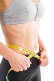 Lean. Sporty lean woman measuring waist. From bust to crotch royalty free stock photos