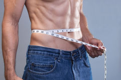 Lean abs measurement. Closeup of shirtless Caucasian man in blue jeans measuring his lean muscular thirty inch waist with tape meaure on gray background royalty free stock photos