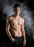 Lean athletic shirtless young man standing on dark background Royalty Free Stock Image