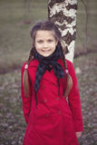 Lean on birch. Smiling child girl in red raincoat lean on birch tree stem Royalty Free Stock Photos