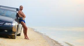 Lean on a car guy at the beach. Man near the car on a sandy beach royalty free stock photos