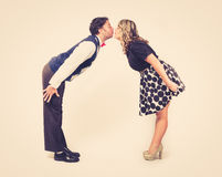 Lean in Kissing Retro. A young male and young female lean in to kiss each other. retro feel against a clean backdrop Royalty Free Stock Images