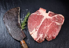 Lean matured raw t-bone steak and vintage cleaver Stock Image