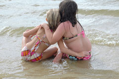Lean On Me. Two little girls hold hands and sit on the banks of a lake or body of water and watch the waves roll in royalty free stock image