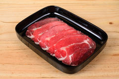 Lean meat. Lean meat in black tray on wooden background royalty free stock photos