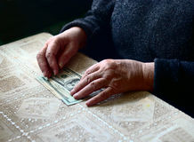 Lean purse. Old woman's hands and dollar bills on table, contrast shot, selective focus, very shallow DOF Royalty Free Stock Photo