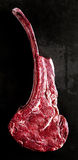 Lean raw tomahawk steak. Lean raw tomahawk beef steak, so called for its shape on the bone, isolated on a black background in a close up overhead view royalty free stock image