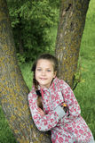 Lean on tree stem. Child girl posing lean on tree stem by summer Stock Images