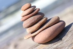 Leaned pebble tower. Close-up, same red color stones on each other Royalty Free Stock Photo