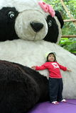 Leaning against giant panda doll Royalty Free Stock Photography