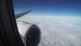 Leaning aircraft passenger window view of airplane turbine above clouds. Leaning aircraft passenger window view of airplane turbine above clouds stock video footage