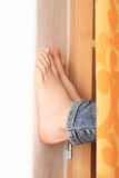 Leaning bare feet. Bare feet of a little girl - child leaning on white wall from curtain Royalty Free Stock Photography