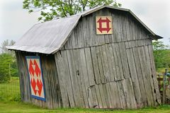 Leaning Barn. A small barn in Ohio, leaning perilously, with two quilt patterns Stock Image