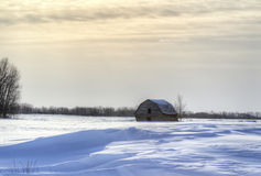 Leaning barn in snow. Weathered leaning barn in winter under a cloudy sky Royalty Free Stock Image