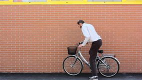 Leaning a Bike against a Brick Wall stock video footage