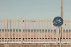 Leaning bike traffic signal and railway fence background. Pesaro, Italy royalty free stock images