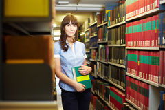 Leaning on book shelf Royalty Free Stock Photography