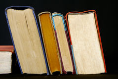 Leaning books. Stack of books leaning against black background Royalty Free Stock Photo