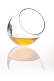 Leaning glass with apple juice. Inside, with reflection from plexi glass Royalty Free Stock Photography