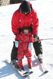 Leaning how to ski. Dad teaching daughter how to ski Royalty Free Stock Image