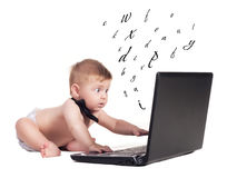 Leaning letters. Cute child looking at laptop with flying letters Stock Photos
