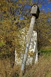 Leaning old birdhouse on pole Royalty Free Stock Images