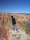 Leaning over the Edge. Young woman peering curiously over the edge of the Grand Canyon in Arizona Royalty Free Stock Photos