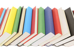 Leaning row of books. Leaning row of colorful books isolated against a white background Royalty Free Stock Photo