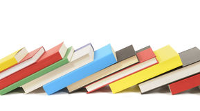 Leaning row of books isolated on a white background, copy space. Leaning row of colorful books isolated against a white background.  Space for copy Stock Images