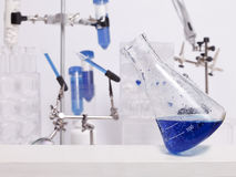 Leaning Science Beaker. A science beaker with a blue liquid balances on its edge in a lab with other science equipment royalty free stock image