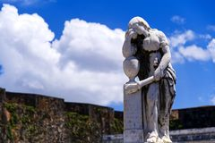 Withered Statue Leaning Against a Grave royalty free stock photos
