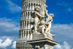 The Leaning Tower of Pisa. Cherub statue that sits on the Field of Miracles in Pisa Italy with the leaning tower in the background stock photo