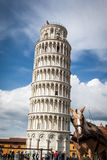 The leaning tower of Pisa with a horse in the foreground. The leaning tower is visited by countless number of tourists each year Royalty Free Stock Photos