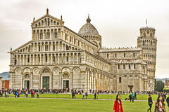 Leaning Tower of Pisa. Italian monuments. Whole view of the cathedral of Pisa with many foreigners and visitors strolling along a green field.nThe Leaning Tower Stock Image