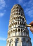 Leaning tower of Pisa, Italy against cloudy bright blue sky through a vintage golden magnifier in hand Stock Images