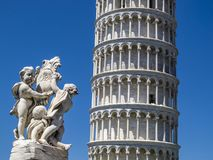 Leaning Tower of Pisa partial view and Putti Fountain sculpture in Piazza dei Miracoli, Square of Miracles in Pisa, Italy stock photography