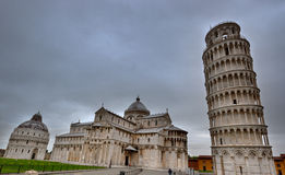 Leaning Tower Pisa Piazza dei Miracoli. Piazza dei Miracoli, the ornate medieval Baptistry, the marble facade of the Duomo and the iconic blind arcade columns of Royalty Free Stock Photography