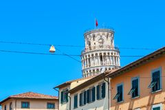 The Leaning Tower of Pisa seen amid typical local buildings royalty free stock photo
