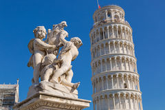 Leaning Tower of Pisa and status of cherubs winged angels in Pis. PISA, ITALY - SEPTEMBER 2016 : Leaning Tower of Pisa and status of cherubs winged angels in Stock Image