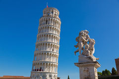 Leaning Tower of Pisa and status of cherubs winged angels in Pis. PISA, ITALY - SEPTEMBER 2016 : World famous Leaning Tower of Pisa and status of cherubs winged Royalty Free Stock Image
